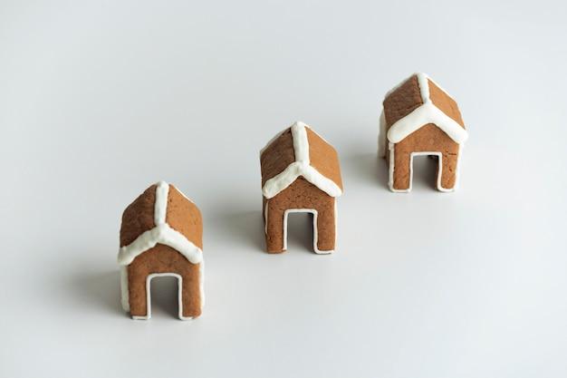 白い背景の上の3つの小さなジンジャーブレッドハウス。クリスマスの焼き菓子。冬の休日のパターン。 Premium写真