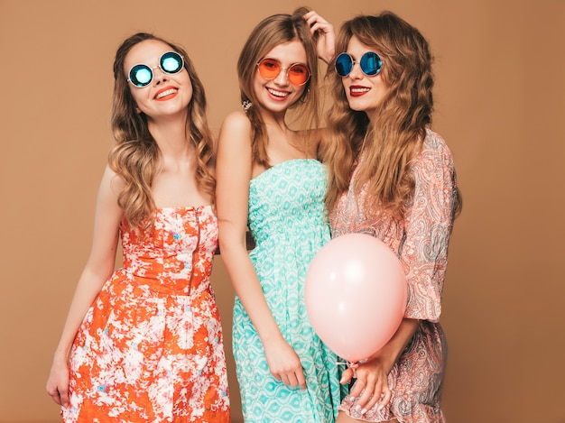 Three smiling beautiful women in checkered shirt summer clothes. girls posing. models with colorful balloons in sunglasses. having fun,ready for celebration birthday or holiday party Free Photo