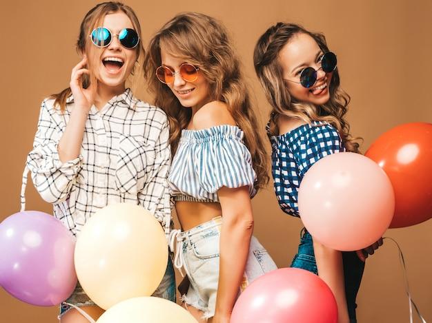 체크 무늬 셔츠 여름 옷과 선글라스에 세 웃는 아름다운 여성. 포즈를 취하는 여자. 다채로운 풍선과 함께 모델입니다. 재미, 축하 생일 파티 준비 무료 사진