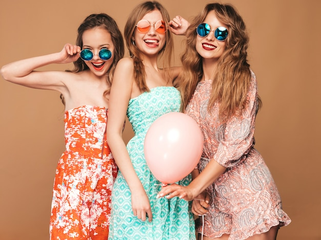 Three smiling beautiful women in summer dresses. girls posing. models with colorful balloons. having fun, ready for celebration birthday or holiday party Free Photo