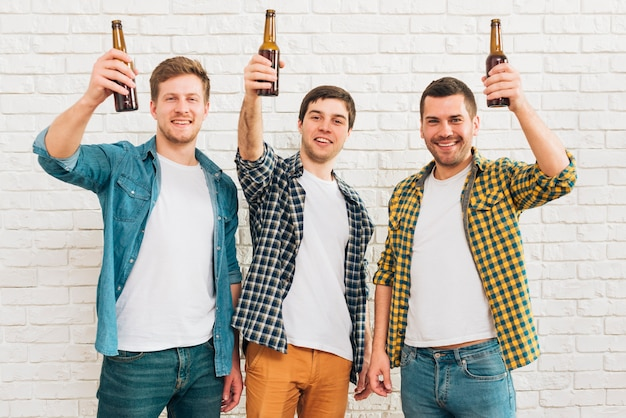 Three smiling male friend raising beer bottle standing against white brick wall Free Photo