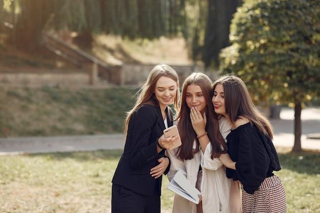 Tre studenti in piedi in un campus universitario Foto Gratuite