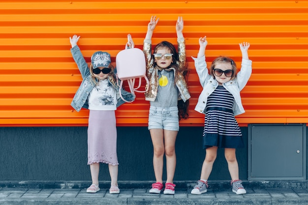 Three stylish cute little girls with their hands raised up Premium Photo