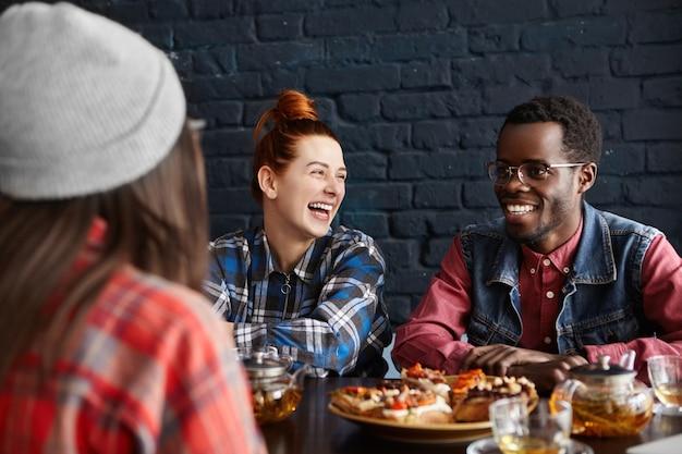 カフェで昼食をとり、お互いに話し、冗談を言って笑っている3人のスタイリッシュな若者 無料写真