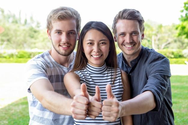 3人の成功した学生の友人が親指を上げている 無料写真