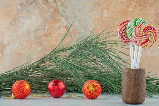 대리석 바탕에 3 개의 크리스마스 공 세 달콤한 다채로운 막대 사탕. 고품질 사진 무료 사진