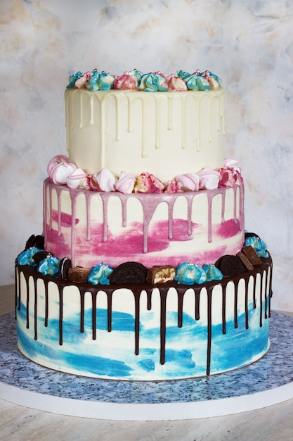 Three-tiered colored cake with colored smudges of chocolate on light. Premium Photo