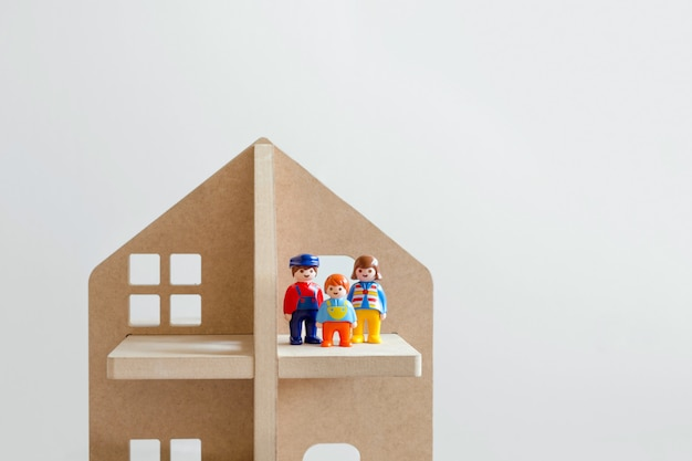Three toy figures of men-a man, a woman and a child in a wooden toy house. Premium Photo