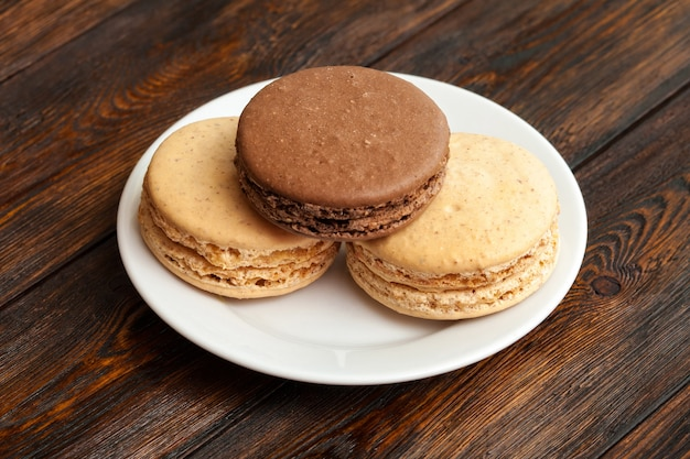 Three traditional french chocolate macarons on plate Premium Photo