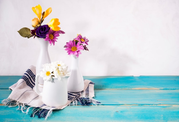 Three vases with bright flowers on table Free Photo