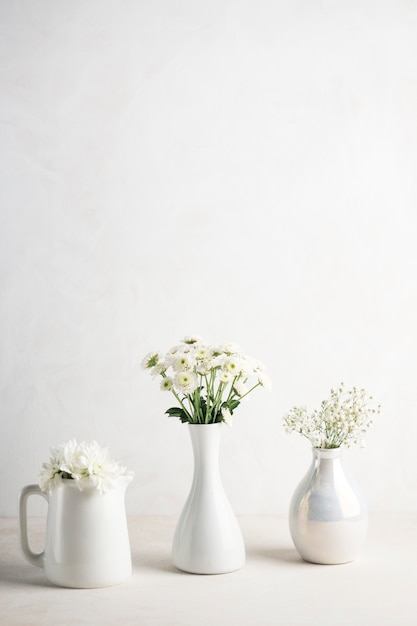 Three vases with flowers on table Free Photo
