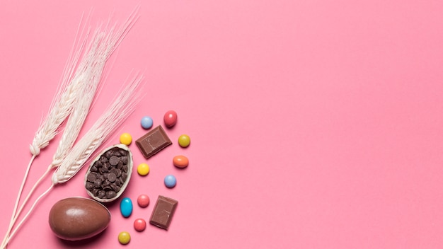 Three wheat ears with chocolate easter eggs and gem candies on pink background Free Photo