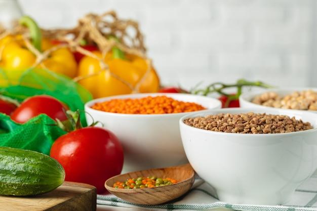 Three white bowls of groats on background of fresh vegetables Premium Photo