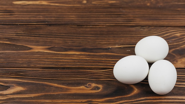 Three white eggs on wooden table Free Photo