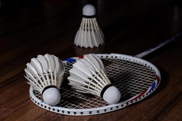 Three white shuttlecocks and a badminton racquet Free Photo