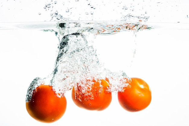 Three whole red tomatoes splashing in water on black background Free Photo
