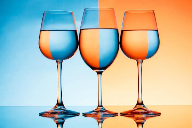 青とオレンジ色の壁を越えて水で3つのワイングラス 無料写真