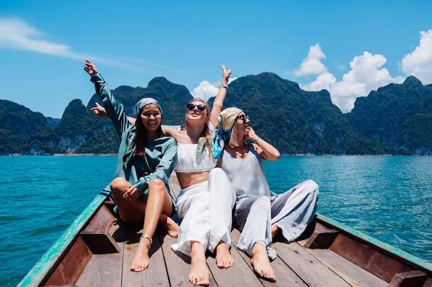 Tre amiche turisti donna viaggiano nel parco nazionale di khao sok, in vacanza in thailandia. navigando sulla barca asiatica sul lago al giorno pieno di sole, con una vista incredibile. Foto Gratuite