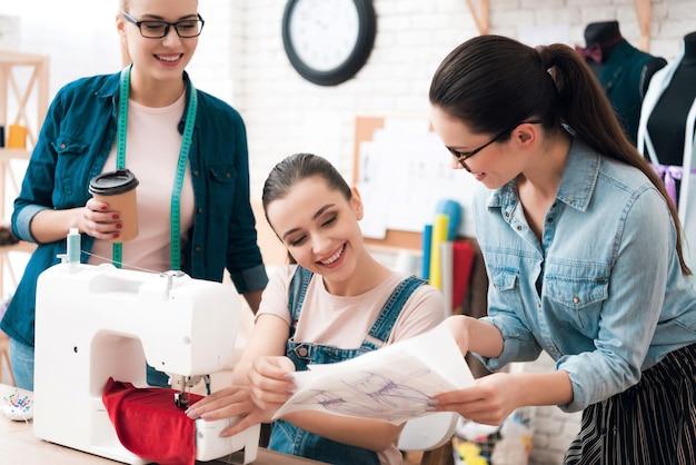Three women in factory sew new clothes. Premium Photo
