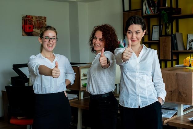 Tre donne impiegati in ufficio guardando la telecamera sorridendo allegramente mostrando i pollici in su lavorando insieme in piedi in ufficio Foto Gratuite