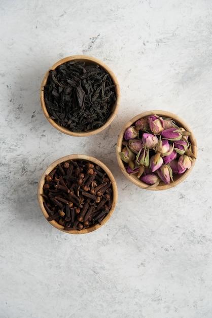 Trois bols en bois avec des roses séchées, des clous de girofle et des thés en vrac.  Photo gratuite