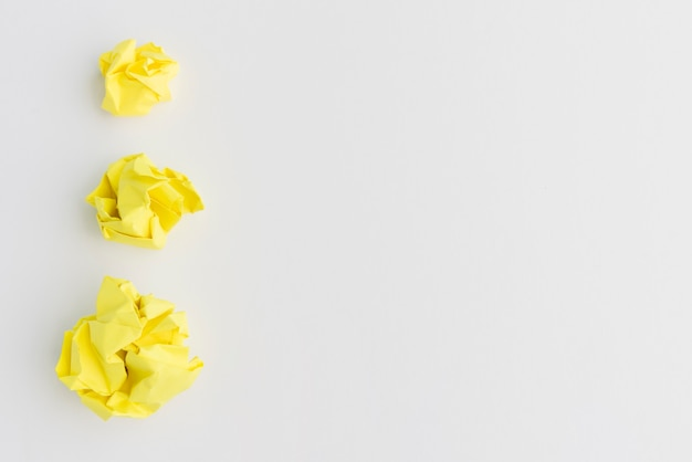Three yellow crumpled paper ball of different sizes against white background Free Photo