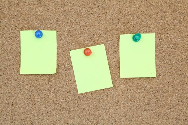Three yellow memo sticker on notice cork board Premium Photo