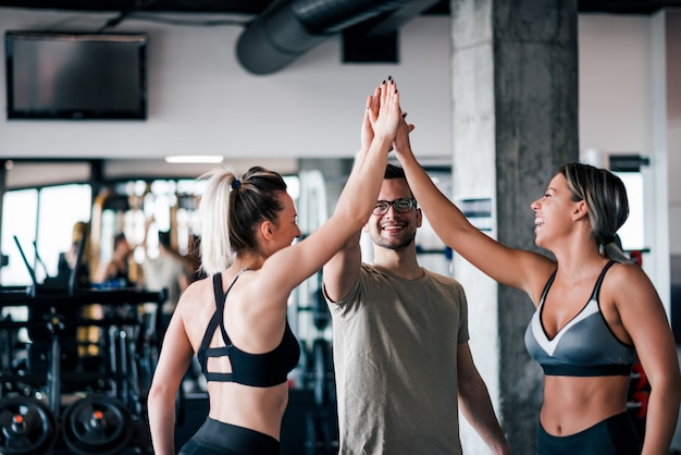 Three young athletic people in sportswear giving high five in gym. Premium Photo