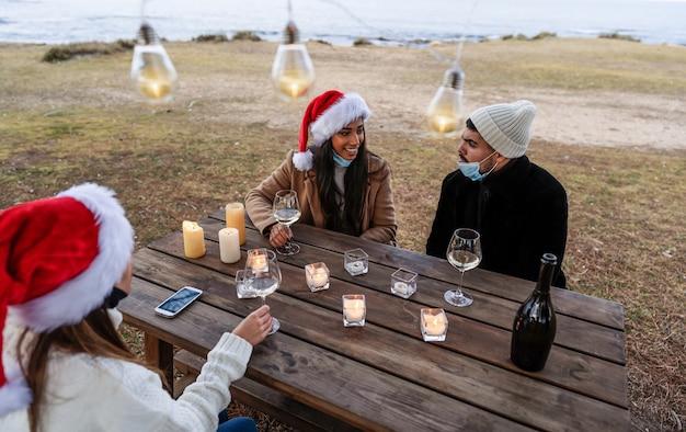 Три молодых красивых человека в шляпе санта-клауса сидят на открытом воздухе и пьют шампанское, празднуют рождество Premium Фотографии