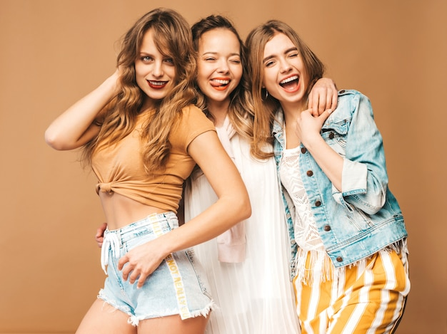 Three young beautiful smiling girls in trendy summer casual clothes. sexy carefree women posing. positive models Free Photo