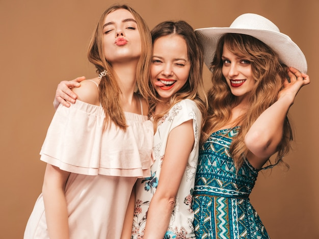 Three young beautiful smiling girls in trendy summer casual dresses. sexy carefree women posing. Free Photo