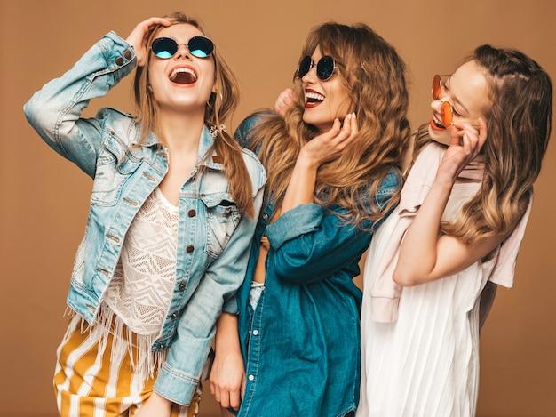 Tre giovani belle ragazze sorridenti in vestiti casuali dei jeans di estate alla moda. posa sexy spensierata delle donne. modelli positivi in occhiali da sole Foto Gratuite