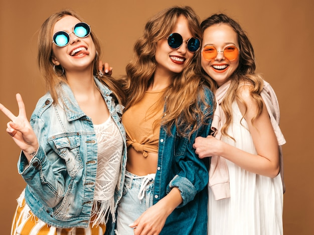 Three young beautiful smiling girls in trendy summer casual jeans clothes. sexy carefree women posing. positive models in sunglasses Free Photo