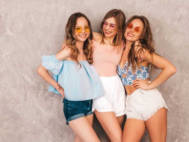 Three young beautiful smiling girls in trendy summer clothes. sexy carefree women posing. positive models having fun. hugging Free Photo