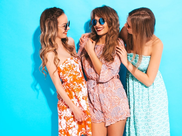 Three young beautiful smiling girls in trendy summer colorful dresses. sexy carefree women in sunglasses. Free Photo