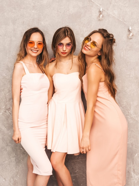Three young beautiful smiling girls in trendy summer light pink dresses. sexy carefree women posing. positive models in round sunglasses having fun Free Photo