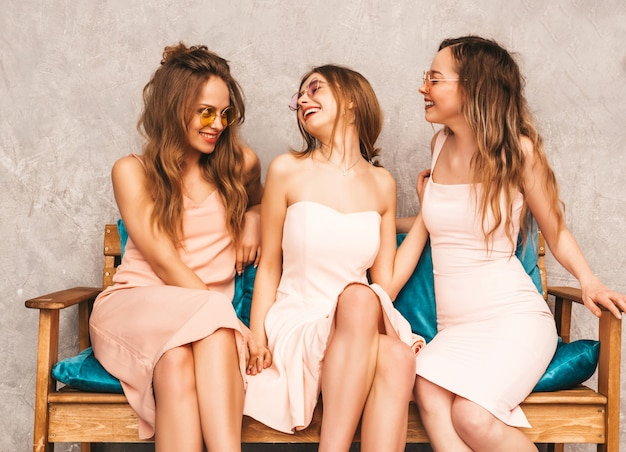 Three young beautiful smiling girls in trendy summer pink dresses. sexy carefree women sitting on sofa in luxury interior. positive models in round sunglasses having fun and communicating Free Photo