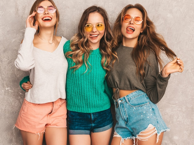 Three young beautiful smiling gorgeous girls in trendy summer clothes.  sexy carefree women posing. positive models having fun in round sunglasses Free Photo