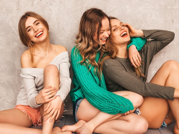 Three young beautiful smiling gorgeous girls in trendy summer clothes.  sexy carefree women posing. positive models having fun. sitting on the floor. hugging Free Photo