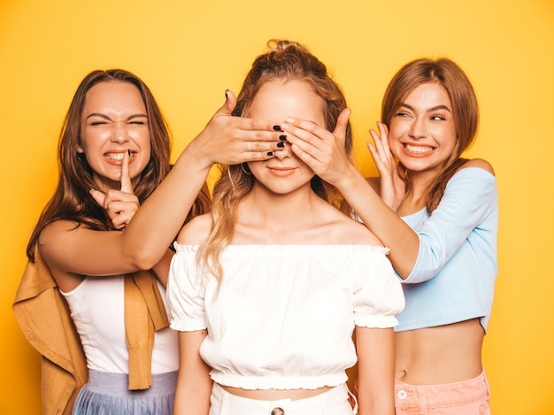 Three young beautiful smiling hipster girls in trendy summer clothes.sexy carefree women posing near yellow wall.models surprising their friend.they cover her eyes and hugging from behind Free Photo