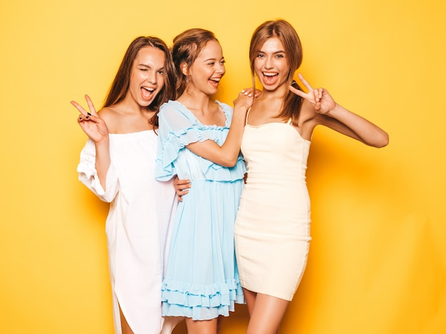 Three young beautiful smiling hipster girls in trendy summer clothes. sexy carefree women posing near yellow wall. positive models going crazy and having fun.shows peace sign Free Photo