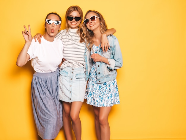 Three young beautiful smiling hipster girls in trendy summer clothes. sexy carefree women posing near yellow wall. positive models having fun in sunglasses.they show tongue Free Photo