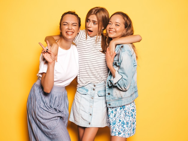 Three young beautiful smiling hipster girls in trendy summer clothes. sexy carefree women posing near yellow wall. positive models having fun Free Photo