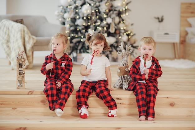 빨간 잠옷을 입은 세 명의 어린이가 아늑한 거실의 침대에 누워 막대기에 달콤한 사탕을 먹습니다. 크리스마스 컨셉입니다. 홈 홀리데이 프리미엄 사진