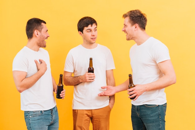 Three young male friends enjoying the beer standing against yellow backdrop Free Photo