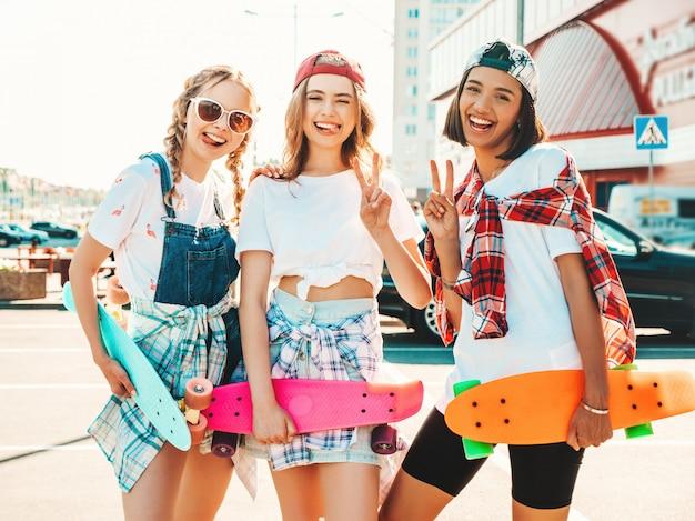カラフルなペニースケートボードと3人の若い笑顔の美しい女の子。通りの背景でポーズをとって夏の流行に敏感な服の女性。楽しさとクレイジーになる肯定的なモデル。ピースサインを表示 無料写真