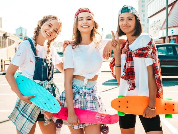 カラフルなペニースケートボードと3人の若い笑顔の美しい女の子。 無料写真