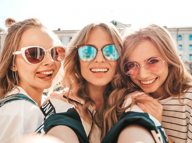 Three young smiling hipster women in summer clothes.girls taking selfie self portrait photos on smartphone.models posing in the street.female showing positive face emotions in sunglasses Free Photo