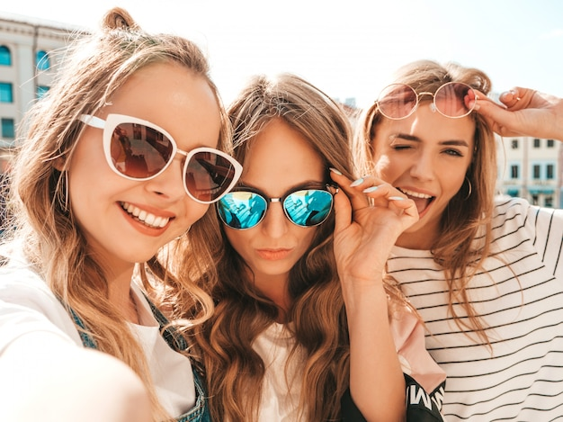 Three young smiling hipster women in summer clothes.girls taking selfie self portrait photos on smartphone.models posing in the street.female showing positive face emotions Free Photo