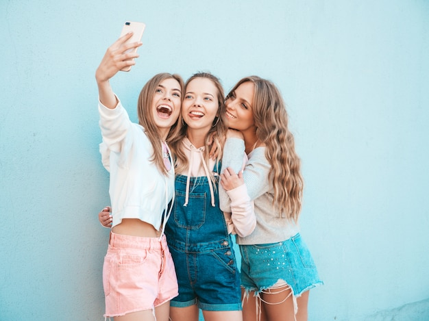 Three young smiling hipster women in summer clothes.girls taking selfie self portrait photos on smartphone.models posing in the street near wall.female showing positive face emotions.showing tongue Free Photo
